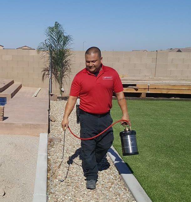 pest control technician spraying the backyard of a house